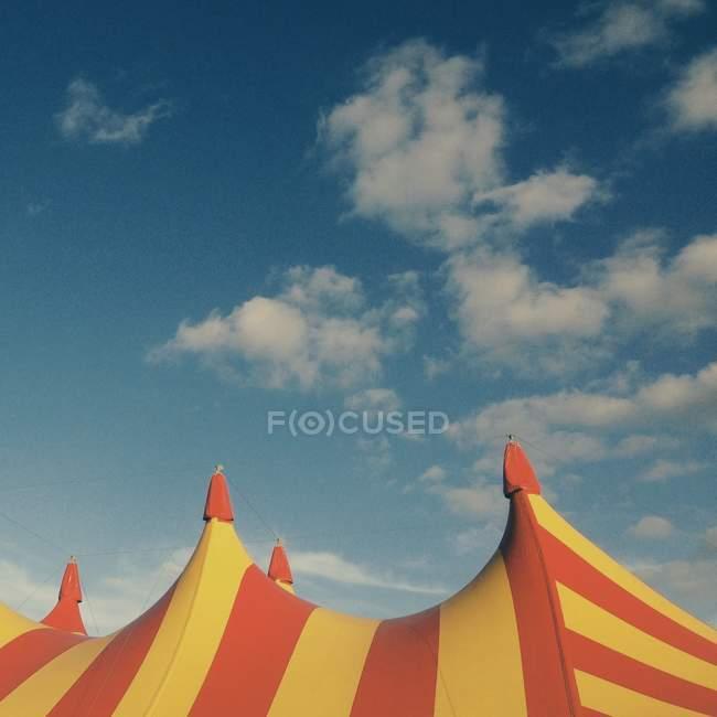 Tent top of circus under cloudy sky — Stockfoto