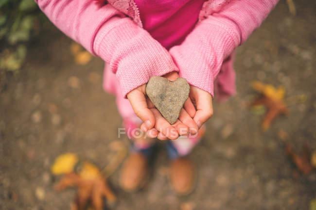 Close-up of Girl holding heart shape stone — Stock Photo