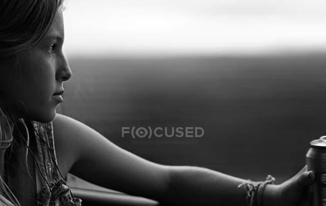 Close-up vista lateral da menina bonita sentado no carro e olhando através da janela — Fotografia de Stock