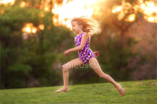 Bambina che indossa costume da bagno saltando nel cortile posteriore — Foto stock