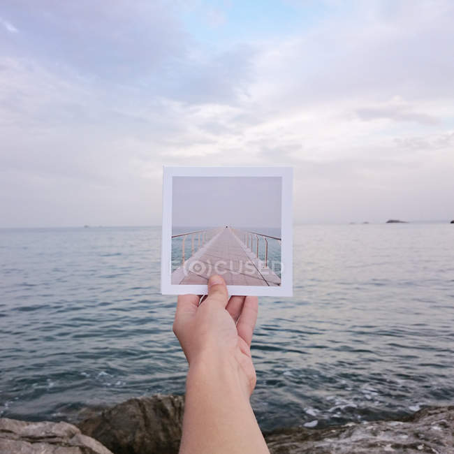 Cropped image of Human hand holding instant print transfer photo in front of the sea — Stock Photo