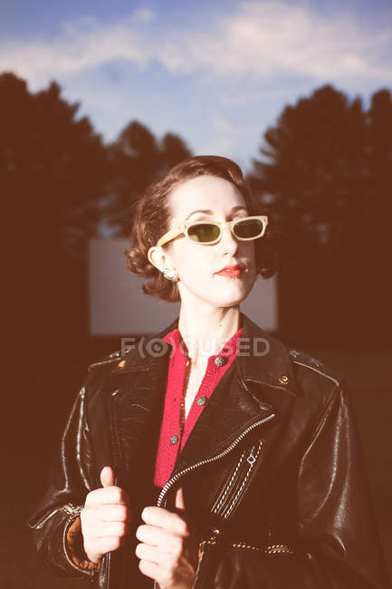Young woman wearing retro sunglasses and leather jacket outdoors — Stock Photo