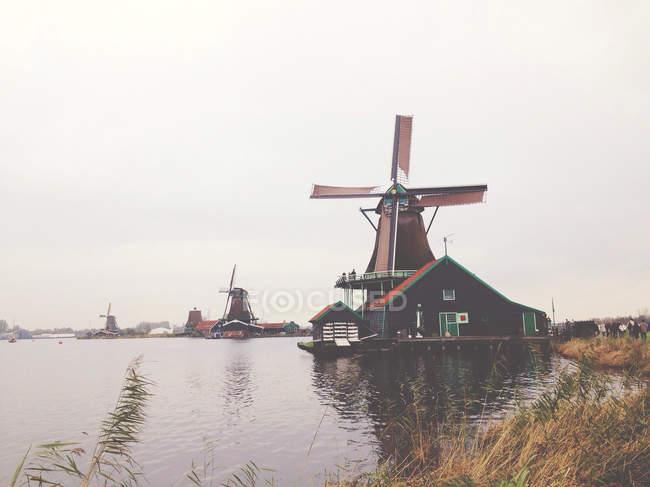 Molinos de viento tradicionales bajo el cielo gris, Kinderdisk, Países Bajos - foto de stock