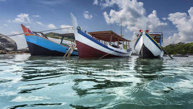 Три лодки, стоящие на якоре на пляже, остров Белитунг, Индонезия — стоковое фото