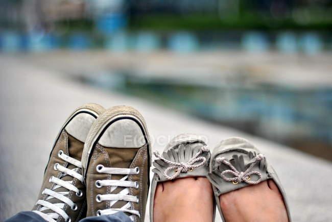 Imagem cortada de casal segurando os pés perto um do outro — Fotografia de Stock