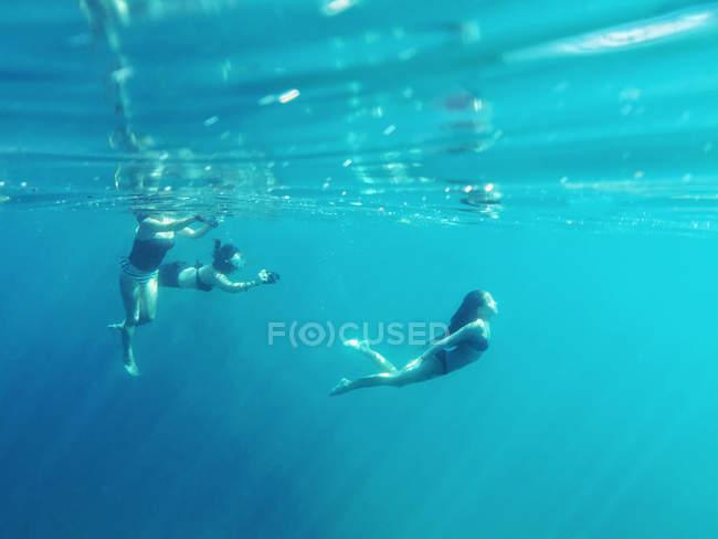 Drei Personen schwimmen gemeinsam im Ozean — Stockfoto