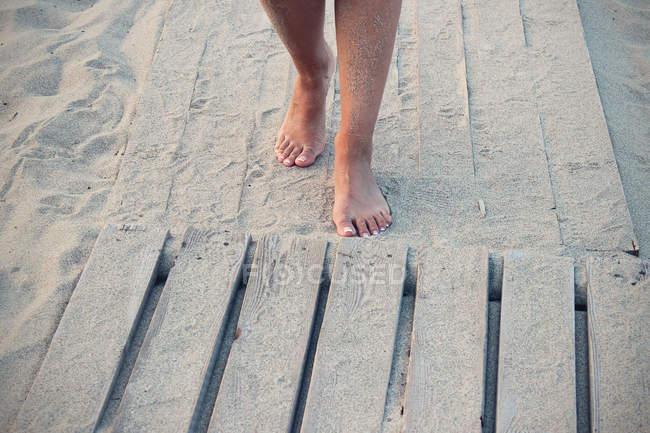 Abgeschnittenes Bild einer Frau, die barfuß am Holzdeck am Strand entlang läuft — Stockfoto