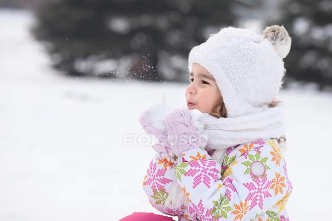 Mädchen bläst im Winter eine Handvoll Schnee — Stockfoto