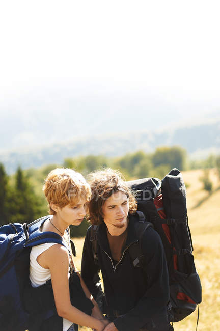 Attractive young caucasian couple at journey with backpacks — Stock Photo