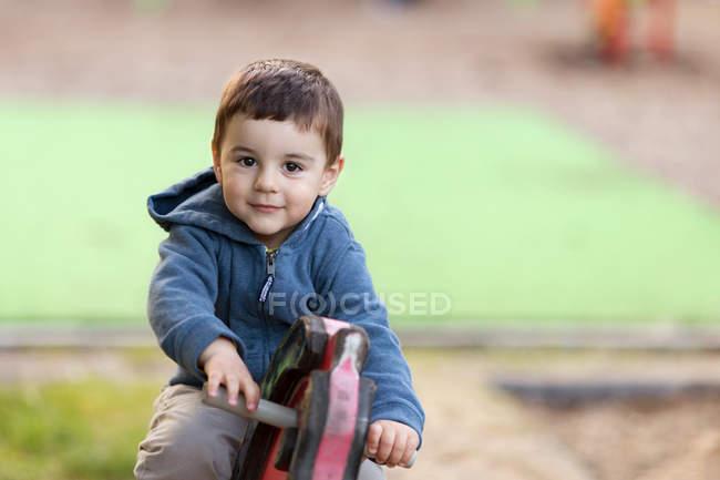Boy sitting on wooden horse on playground — Stock Photo
