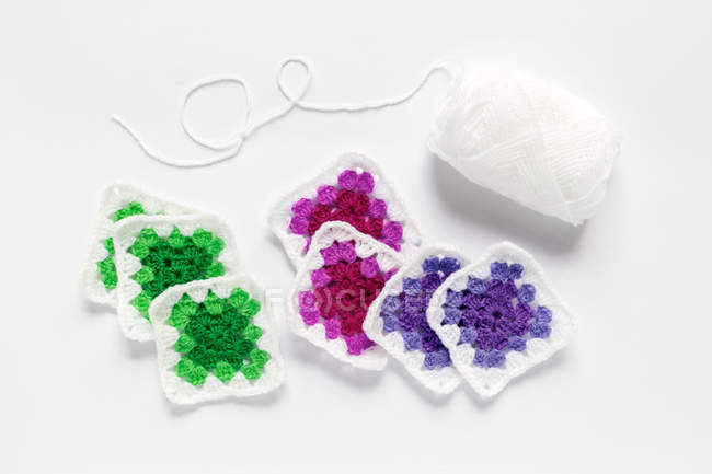 Crocheted doilies and yarn against white background — Stock Photo