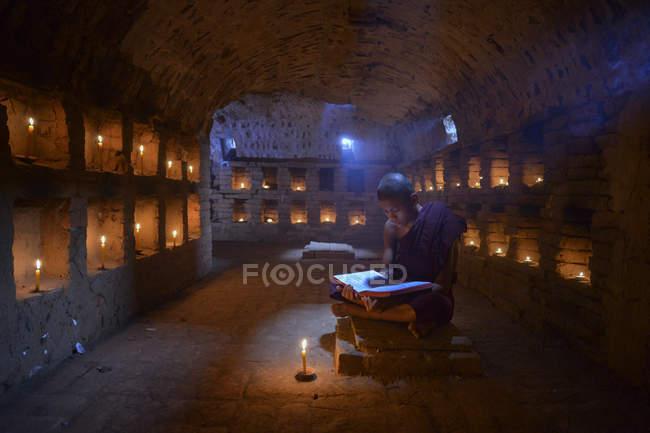Monje novicio sentado en el templo, Myanmar - foto de stock