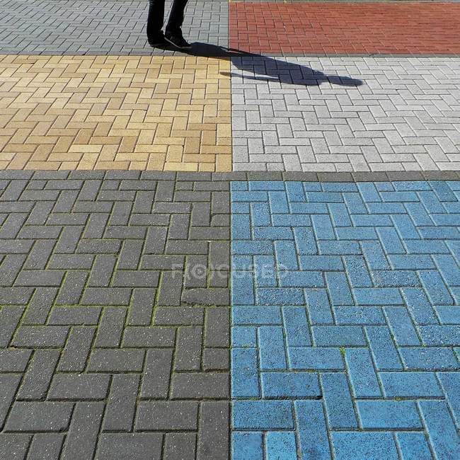 Human shade on multi colored pavement — Stock Photo