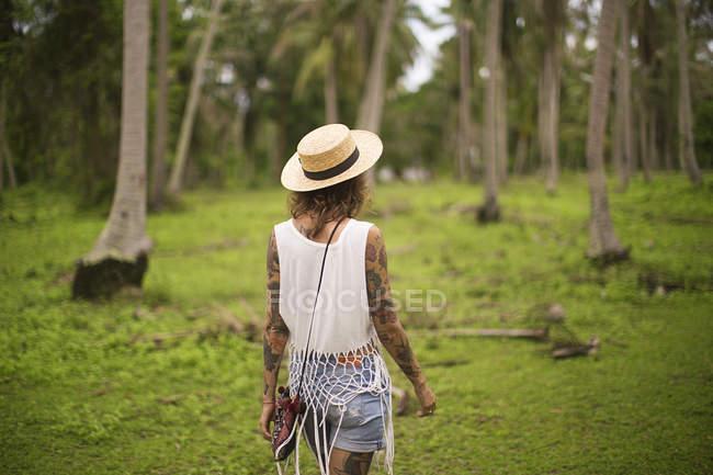 Rear view of a woman walking in a tropical garden, Thailand — Stock Photo