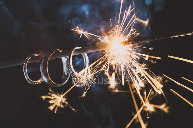 Wedding Rings hang on a sparkler as it burns down illuminating the rings — Stock Photo