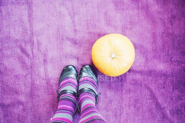 Ноги в фиолетовый полосатые носки рядом с тыквой — стоковое фото