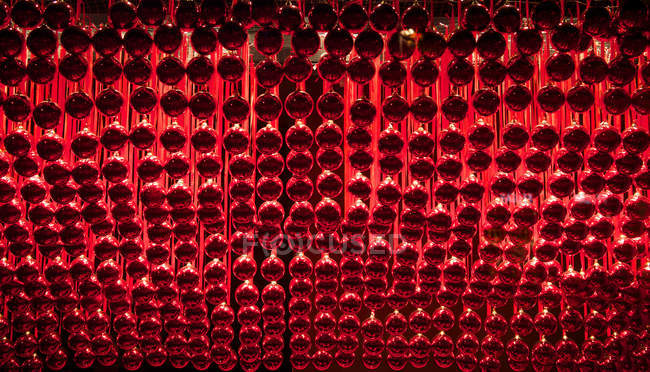 Low angle view of rows of hanging red baubles — Stock Photo
