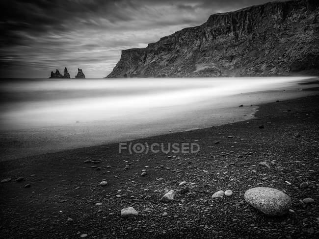 Монохромное изображение морских стеков с пляжа в Вике, Исландия — стоковое фото