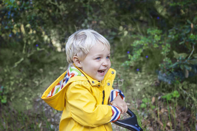 Portrait of smiling toddler boy in raincoat outdoors — Stock Photo