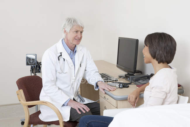 Doctor talking to female patient in examination room — Stock Photo