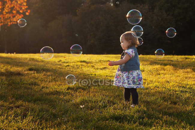 Fille debout entouré de bulles de savon dans le parc — Photo de stock