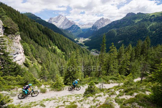 Мужчина и женщина катаются на горных велосипедах по тропе, Доломиты, Италия — стоковое фото