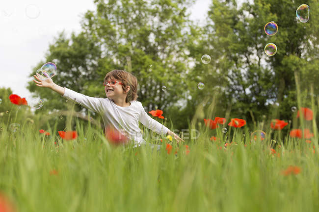 Boy playing with soap bubbles in a poppy field — Stock Photo