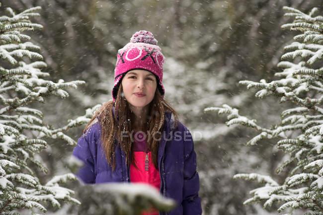 Улыбающаяся девушка, стоящая в лесу на снегу — стоковое фото