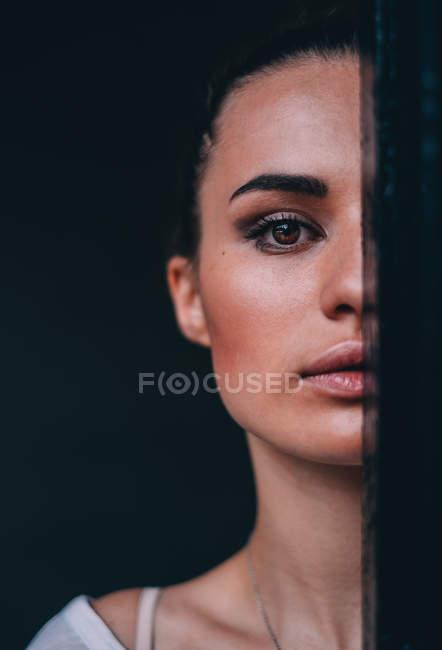 Ritratto di una bella donna che si nasconde mezza faccia dietro una tenda — Foto stock