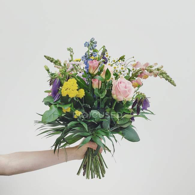 Female hand holding bouquet of beautiful flowers on grey background — Stock Photo