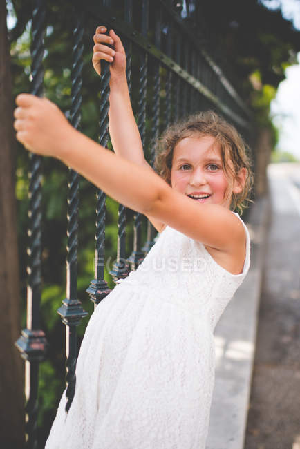Smiling girl hanging from metal railings outdoors — Stock Photo