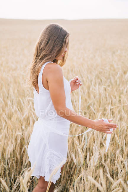 Beautiful woman in white dress standing in wheat field — Stock Photo