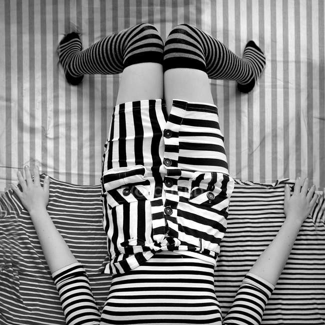 Elevated view of young woman wearing striped clothes and lying on bed, monochrome — Stock Photo