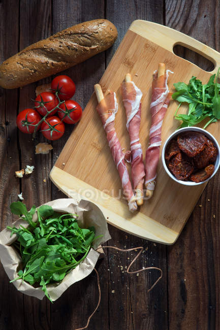 Breadsticks wrapped in parma ham with tomatoes, rocket and bread — Stock Photo
