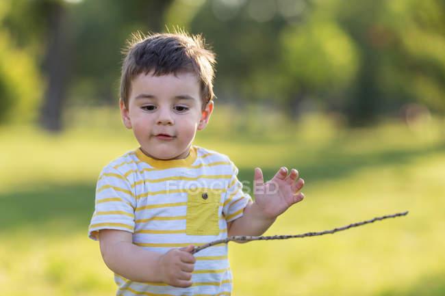 Мальчик, держа палку и работает на открытом воздухе — стоковое фото