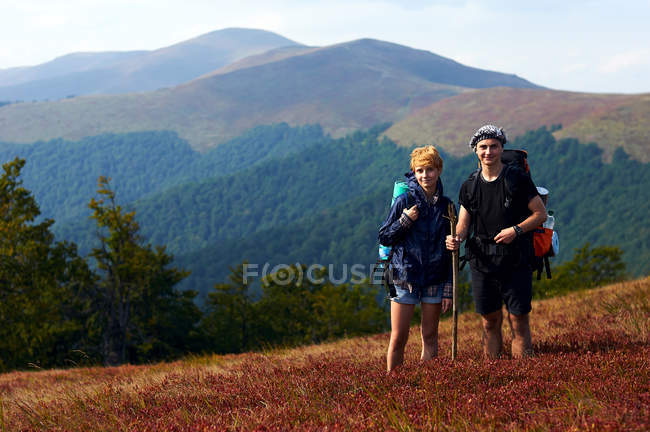 Couple of young caucasian travelers posing at mountains with backpacks — Stock Photo