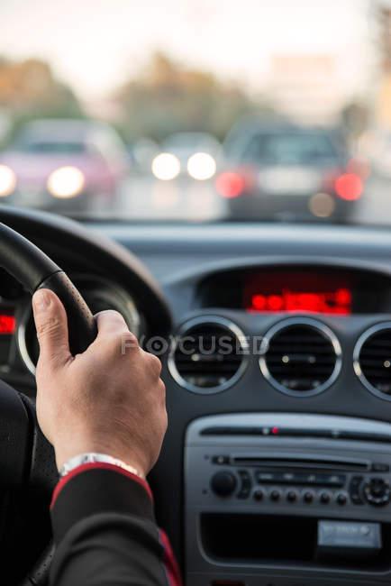 Обрезанное изображение человека за рулем автомобиля на дороге, вид из кабины — стоковое фото