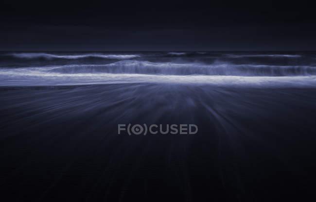 Wellen am schwarzen Sandstrand bei Nacht, Jökulsárlón, Vatnajökull, Island — Stockfoto
