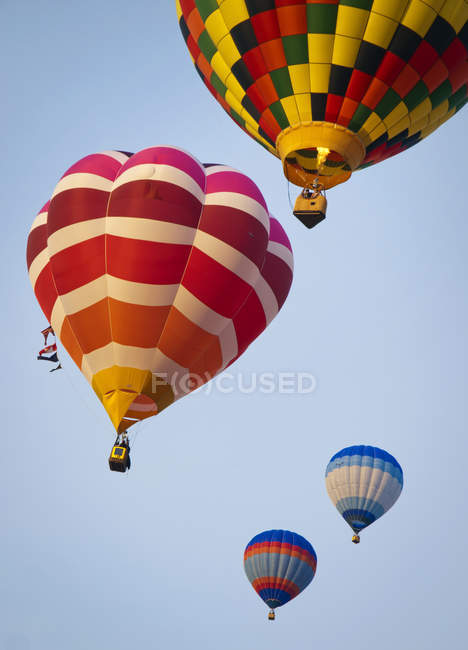 Scenic view of hot air balloons mid air - foto de stock
