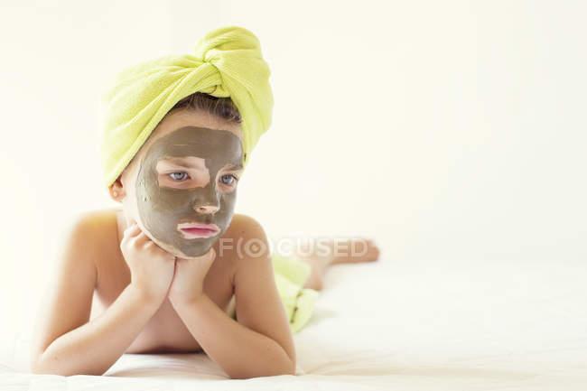 Portrait d'une fille avec masque facial et serviette turban sur la tête — Photo de stock