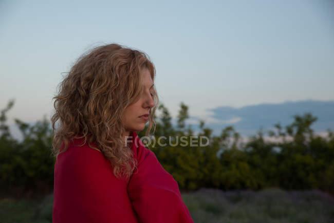Жінка з очі закриті стоячи на відкритому повітрі, загорнутий у ковдру — стокове фото