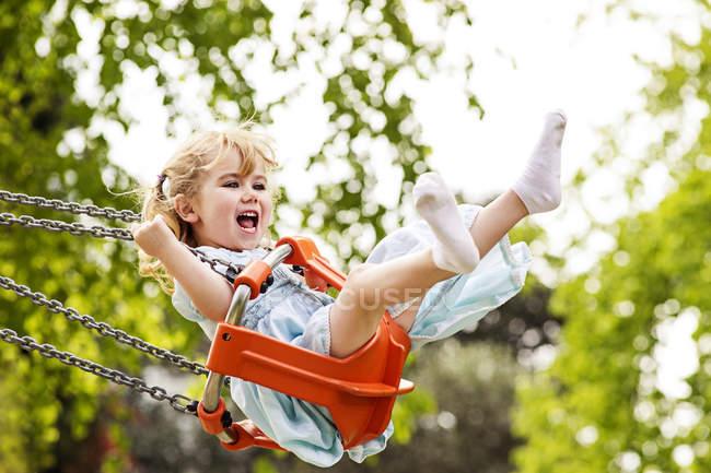Felice ragazza con la bocca aperta su swing — Foto stock