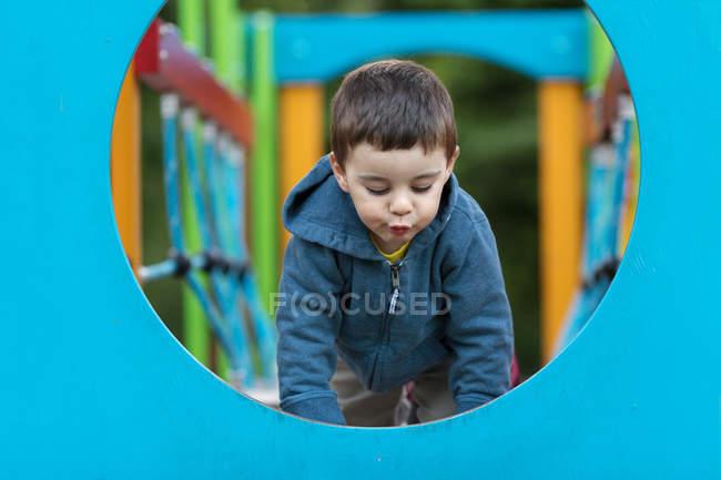 Garçon jouant sur l'équipement dans l'aire de jeu pour l'alpinisme — Photo de stock