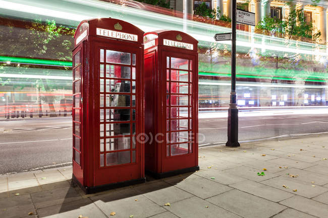 Scenic view of light trails in central London and telephone boxes, UK — Stock Photo