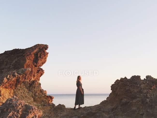 Woman standing between rocks next to ocean at sunset — Stock Photo
