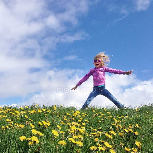 Girl jumping in a field of dandelions with cloudy sky on background — Stock Photo