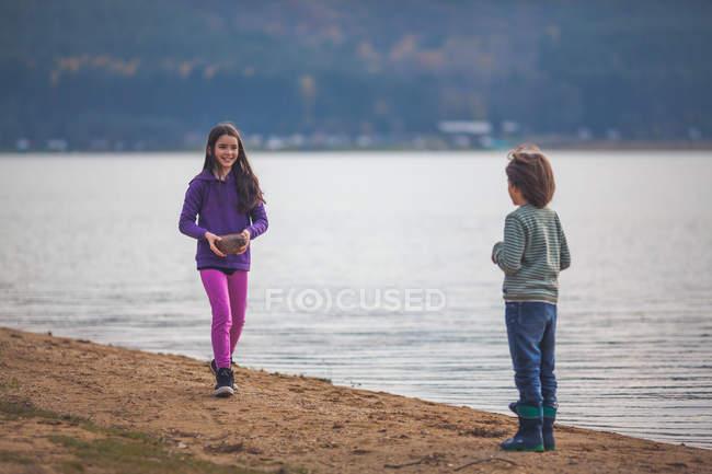 Junge und Mädchen amüsieren sich am See — Stockfoto