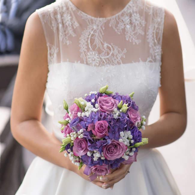 Image de la section médiane de mariée en belle robe tenant le bouquet de mariée — Photo de stock