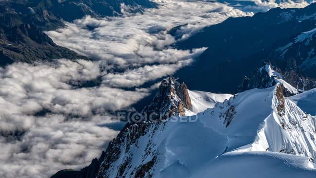 Schneebedeckte Berggipfel und Wolken. aiguille du midi mountain, mont blanc massiv, alpen, chamonix, frankreich — Stockfoto