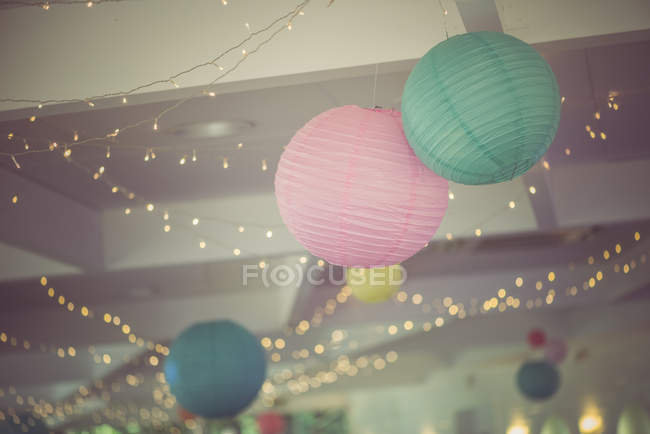 Colored lanterns and fairy lights on party — Stock Photo